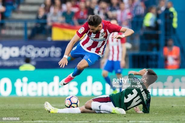 Aitor Bunuel Redrado of Osasuna trips up with Yannick Ferreira Carrasco of Atletico de Madrid during the La Liga match between Atletico de Madrid vs...