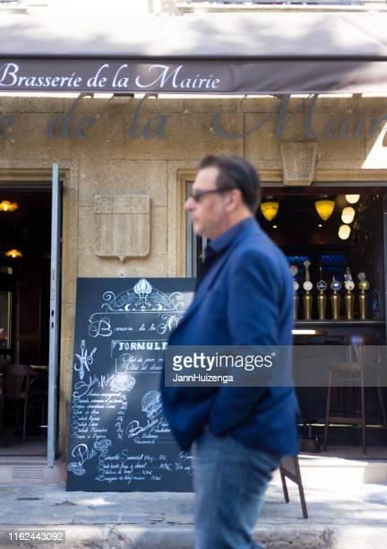 aix-en-provence, france: chic man walks past brasserie - aix en provence stock pictures, royalty-free photos & images