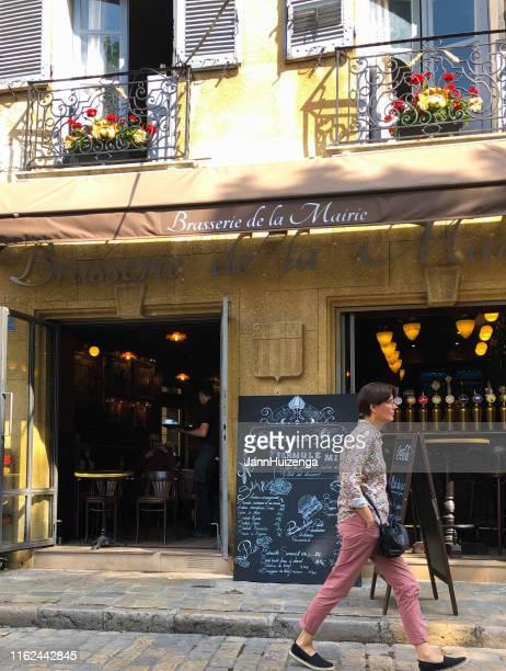 aix-en-provence, france: chic woman walks past brasserie - aix en provence stock pictures, royalty-free photos & images