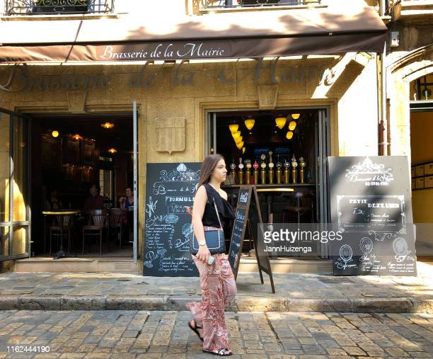 aix-en-provence, france: chic young woman walks past brasserie - aix en provence stock pictures, royalty-free photos & images