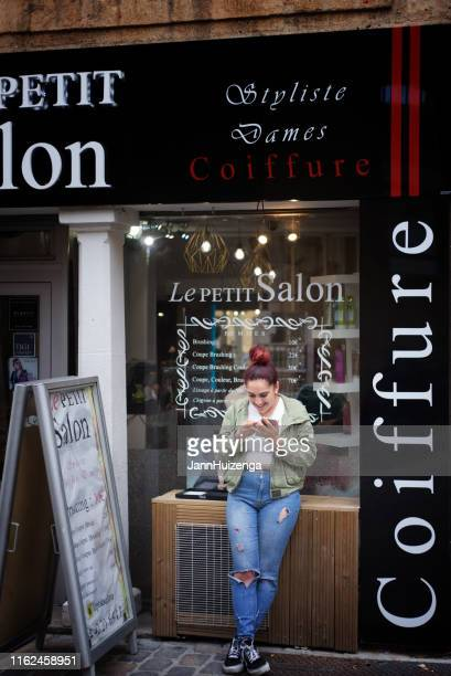 aix-en-provence, france: hip young woman peers at smart phone - aix en provence stock pictures, royalty-free photos & images