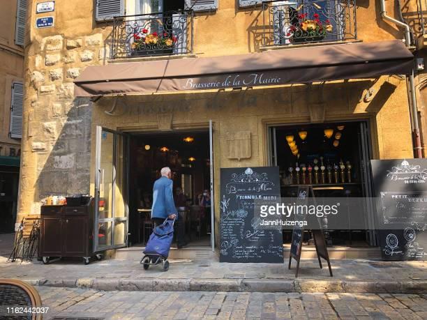 aix-en-provence, france: senior man enters brasserie - aix en provence stock pictures, royalty-free photos & images