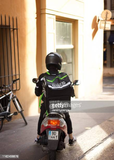 aix-en-provence, france: uber eats delivery person on motorbike - aix en provence stock pictures, royalty-free photos & images