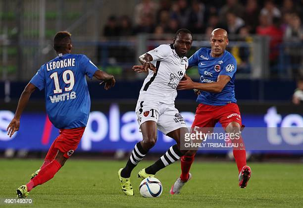Ajaccio's Cameroonian forward Jacques Zoua vies with Caen's French defender Ala eddine Yahia and Caen's French midfielder Jordan Leborgne during the...