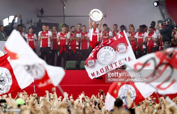 Ajax Amsterdam players celebrate with their fans as they celebrate their club's 34th national champion title after winnning the 2019 Dutch Eredivisie...