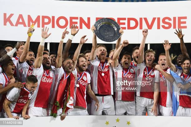 Ajax Amsterdam's captain Matthijs de Ligt holds the champions plate as he celebrates with team mates their Dutch Eredivisie football league's...
