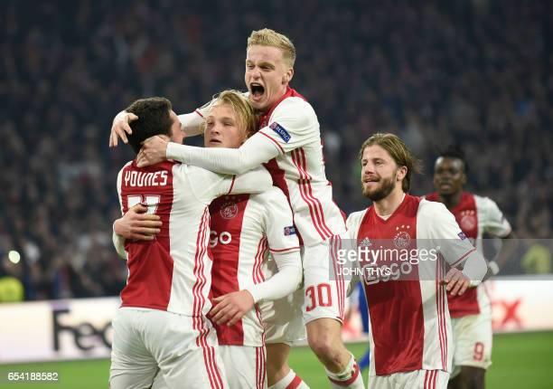 Ajax Amsterdam's forward Kasper Dolberg celebrates with his teammates after scoring on a penalty kick during the UEFA Europa League Round of 16...