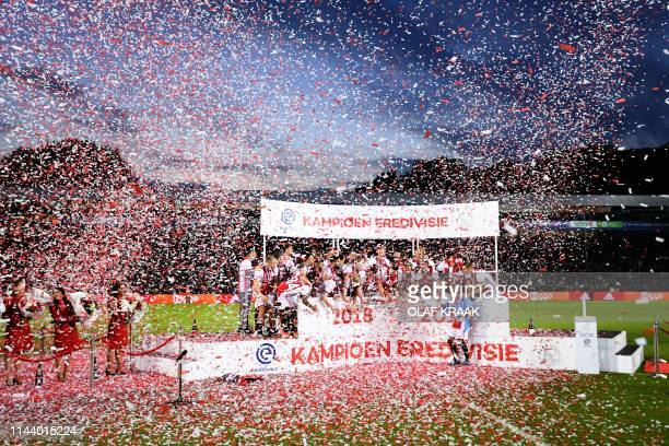 TOPSHOT Ajax Amsterdam's players celebrate their Dutch Eredivisie football league's champion title after the match after De Graafschap Doetinchem on...