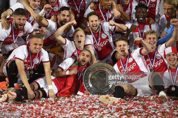Ajax Amsterdam's players celebrate their Dutch Eredivisie football league's champion title after the match after De Graafschap Doetinchem on May 15...