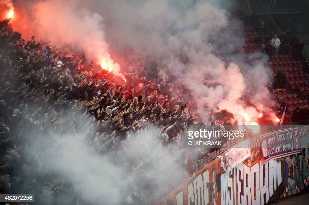Ajax Amsterdam's supporters burn flares and wave hands during a training session of the team in the Amsterdam Arena on January 24 2015 Ajax Amsterdam...