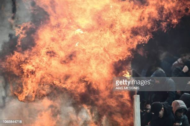 TOPSHOT Ajax fans try to shield themselves from flames during clashes with Greek riot police prior to the start of the UEFA Champions League football...