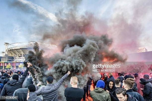 Ajax fans wave flares outside the Johan Cruyff Arena prior to the UEFA Champions League semi-final second leg football match between Ajax Amsterdam...