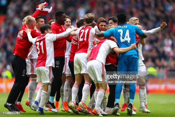 Ajax players celebrate on the pitch winning Eredivisie title as they watch on a big screen PSV losing its match against AZ Alkmaar at the end of the...