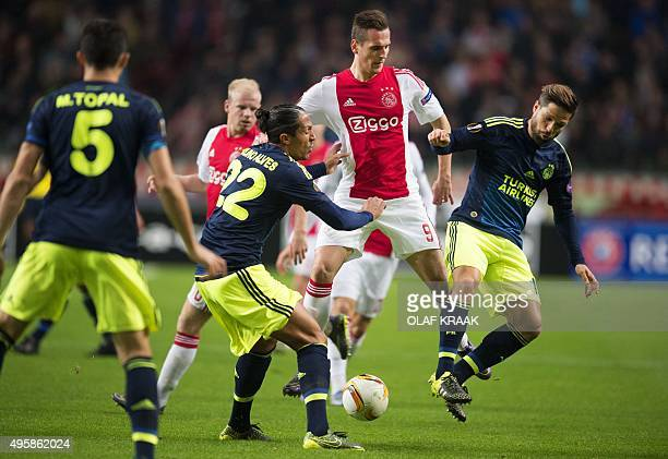 Ajax' Polish striker Arek Milik vies with Fenerbahce's Brazilian midfielder Diego and Portuguese defender Bruno Alves during the UEFA Europa League...
