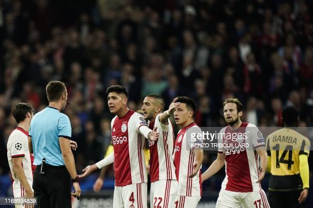 Ajax'Mexican midfielder Edson Alvarez Ajax's Moroccan midfielder Hakim Ziyech and Ajax's Dutch defender Daley Blind react as they speak with Serbian...