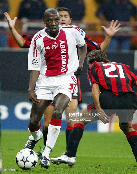 AFC Ajax's Abubakari Yakubu challenges AC Milan's Andrea Pirlo as teammate Alessandro Costacurta gestures during their Champions league group H match...