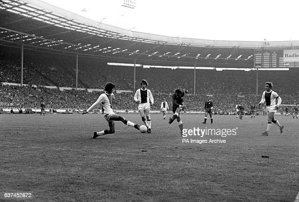 Ajax's Barry Hulshoff blocks a shot from Panathinaikos' Aristidis Kamaras watched by teammate Gerrie Muhren and captain Velibor Vasovic