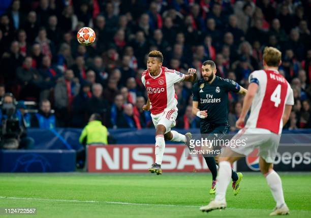 Ajax's Brazilian forward David Neres heads the ball in front of Real Madrid's French forward Karim Benzema during the UEFA Champions league round of...