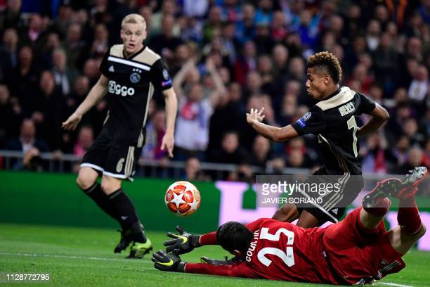 Ajax's Brazilian forward David Neres scores against Real Madrid's Belgian goalkeeper Thibaut Courtois during the UEFA Champions League round of 16...