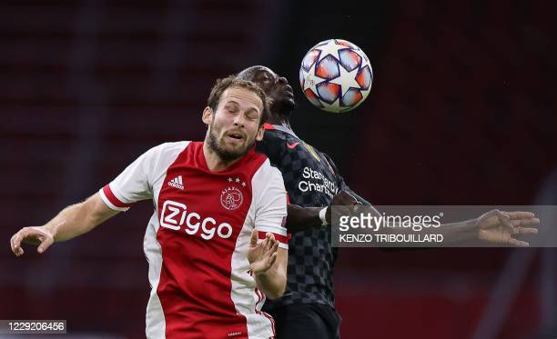 Ajax's Dutch defender Daley Blind jumps for the ball with Liverpool's English midfielder Curtis Jones during the UEFA Champions League Group D...