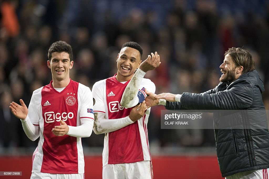 Ajax's Dutch defender Kenny Tete (C) and Danish midfielder Lasse Schone (R) celebrate after winning the UEFA Europa League Group G football match between Ajax Amsterdam and Panathinaikos at the Amsterdam Arena in Amsterdam on November 24, 2016. / AFP / ANP / Olaf KRAAK / Netherlands OUT