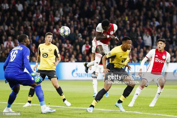 Ajax's Dutch forward Quincy Promes heads the ball and scores past Lille's French goalkeeper Mike Maignan during the UEFA Champions league Group H...