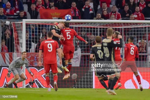 Ajax's Dutch midfielder Dani de Wit and Bayern Munich's German defender Mats Hummels clash heads during the UEFA Champions League Group E football...