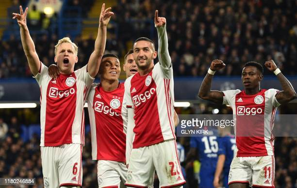 Ajax's Dutch midfielder Donny Van de Beek celebrates with teammates after scoring their fourth goal during the UEFA Champion's League Group H...