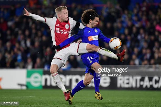 Ajax's Dutch midfielder Donny Van de Beek challenges Getafe's Spanish defender Marc Cucurella during the Europa League round of 32 football match...