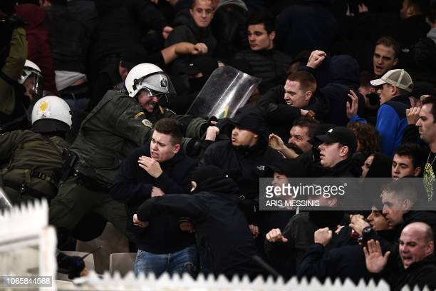 TOPSHOT Ajax's fans clash with Greek riot police prior to the start of the UEFA Champions League football match between AEK Athens FC and AFC Ajax at...