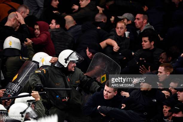 TOPSHOT Ajax's fans clash with the Greek riot police prior to the start of the UEFA Champions League football match between AEK Athens FC and AFC...