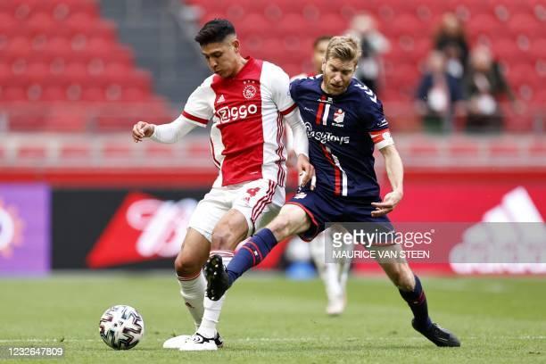 Ajax's Mexican defender Edson Alvare fights for the ball against FC Emmen's Dutch forward Michael de Leeuw during the Dutch Eredivisie football match...