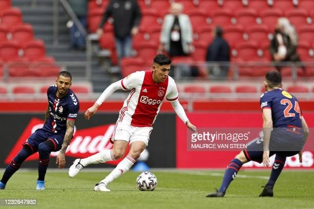 Ajax's Mexican defender Edson Alvare fights for the ball against FC Emmen's Peruvian midfielder Sergio Pena and teammate French midfielder Lucas...