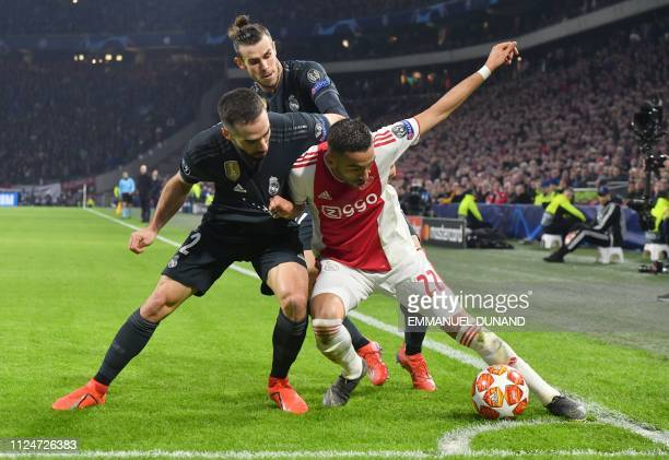 TOPSHOT Ajax's Moroccan midfielder Hakim Ziyech fights for the ball with Real Madrid's Spanish defender Dani Carvajal and Real Madrid's Welsh forward...