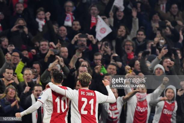 Ajax's Serbian forward Dusan Tadic celebrates with Ajax's Dutch midfielder Frenkie de Jong after scoring their second goal during the UEFA Champions...