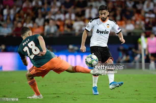 Ajax's US defender Sergino Dest challenges Valencia's Spanish defender Jaume Costa during the UEFA Champions League Group H football match between...