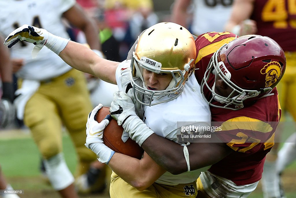 Ajene Harris #27 of the USC Trojans tackles Chris Finke #10 of the Notre Dame Fighting Irish in the third quarter at Los Angeles Memorial Coliseum on November 26, 2016 in Los Angeles, California.