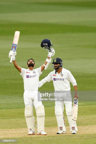 Ajinkya Rahane of India raises his bat after scoring 100 runs during day two of the Second Test match between Australia and India at Melbourne...