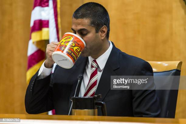 Ajit Pai chairman of the Federal Communications Commission drinks from an oversized coffee mug during an open meeting in Washington DC US on Thursday...