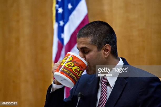 Ajit Pai chairman of the Federal Communications Commission drinks from an oversized coffee mug during an open commission meeting in Washington DC US...