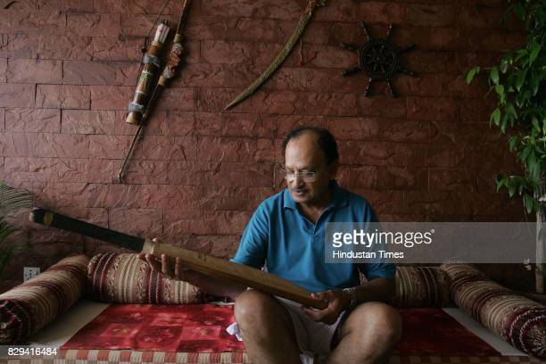 Ajit Wadekar examines his 1960s bat at his home in Worli