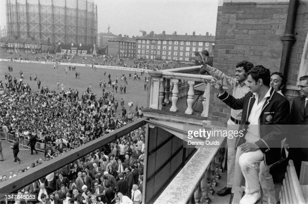 Ajit Wadekar team captain of India and bowler Bhagwath Chandrasekhar wave from the pavilion balcony to the crowd on the pitch below after India won...