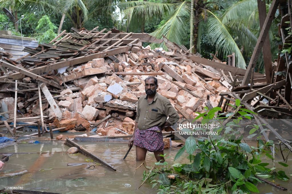 Ajith Prasad stands in front of the rubble of his house on the