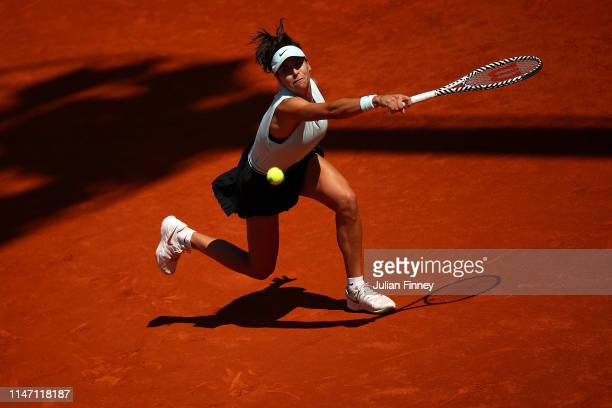 Ajla Tomljanovic of Australia stretches for a backhand in her match against Mihaela Buzarnescu of Romania during day two of the Mutua Madrid Open at...
