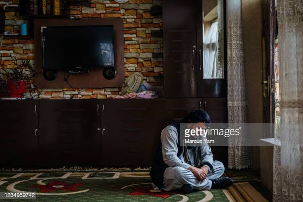 Ajmal Ahmadi, weeps alone in a room after members of his family were killed on Sunday, in an American drone strike that targeted and hit a vehicle in...