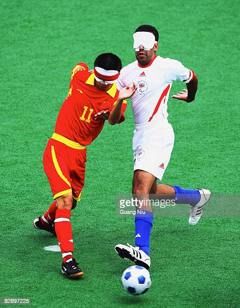 Ajmal Maqsood Ahmed of Great Britain fights a ball with China's Wang Yafeng in the FiveASide Football match during the Beijing Paralympics at Olympic...