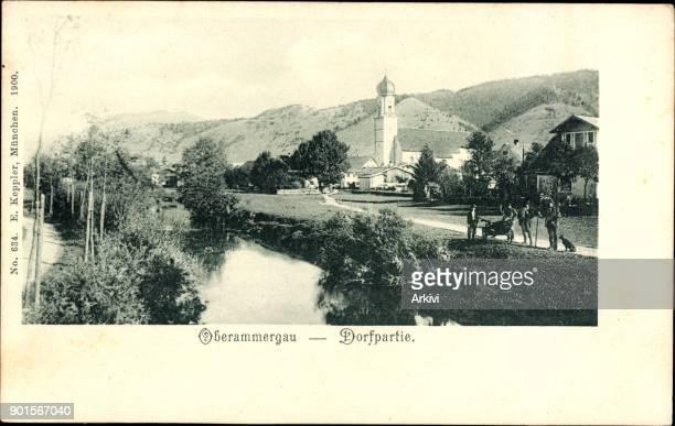Ak Oberammergau in Oberbayern Dorfpartie mit Fluss und Kirche