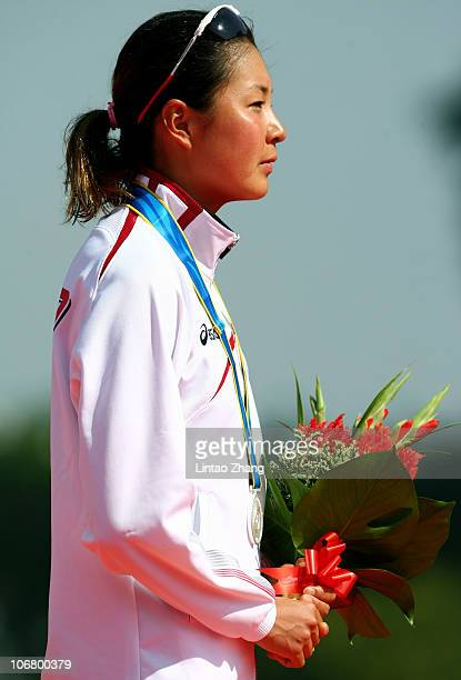 Akane Tsuchihashi of Japan listens to her national anthem with the Silver medal won in the Women's Individual Triathlon at the Triathlon Venue during...