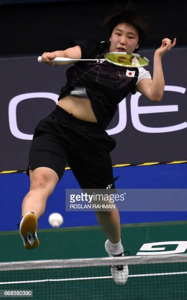 Akane Yamaguchi of Japan hits a return against Zhang Beiwen of the US during their women's singles quarterfinal match at the Singapore Open badminton...