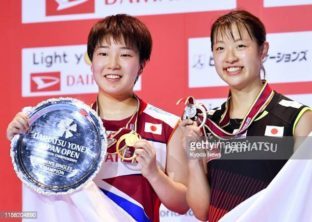 Akane Yamaguchi of Japan poses after winning the women's singles at Japan Open in Chofu Tokyo on July 28 together with runnerup Nozomi Okuhara also...